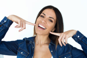 young woman with perfect smile for her low fees and in house insurance within budget